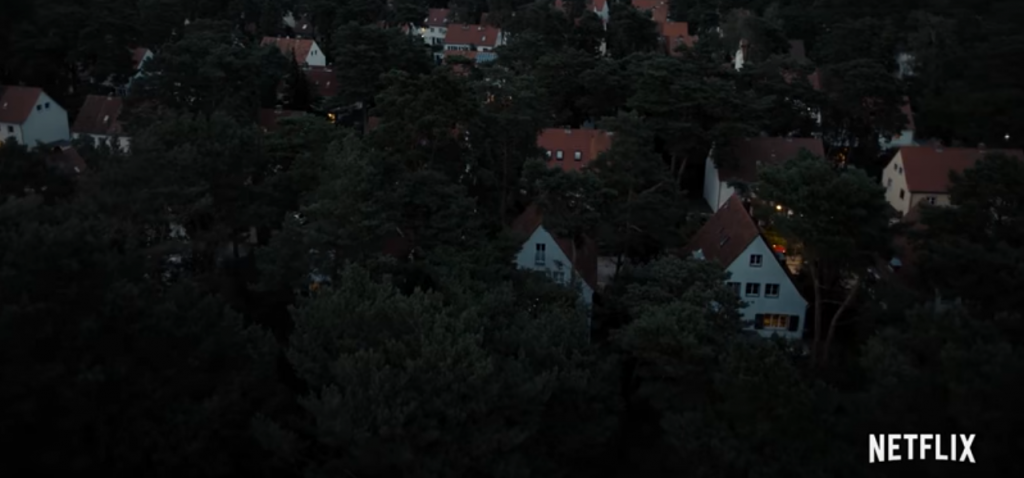 Um cenário visto de cima, mostrando parte da floresta e das casas