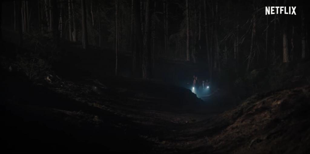 Floresta à noite, com pessoas lá no fundo utilizando uma lanterna